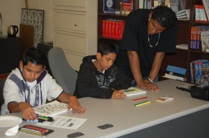 GAP Teen Instructor Zaid Vargas assists Javier and Oscar with adding 3D and perspective to thier first pieces.